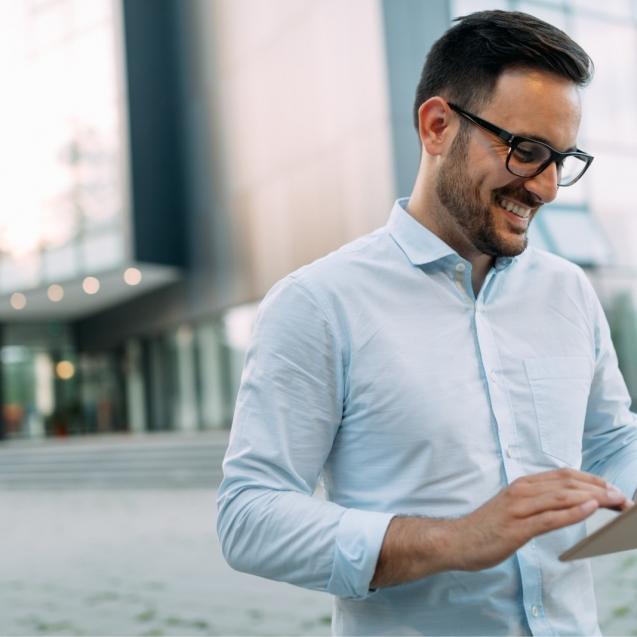 portrait-of-businessman-in-glasses-holding-tablet-AWVHCJ67U